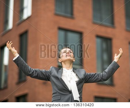 Relaxed Modern Business Woman Against Office Building Rejoicing