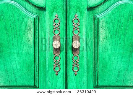 Stylish brass door handles on a hardwood cabinet or closet with ornate escutcheons and raised panels on the doors in a close up frontal view conceptual of furnishing and interior decor poster