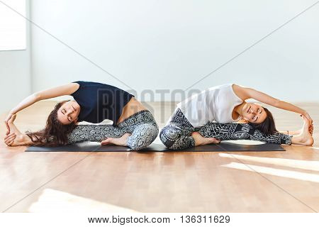 Two Young Women Doing Yoga Asana Revolved Head To Knee Pose