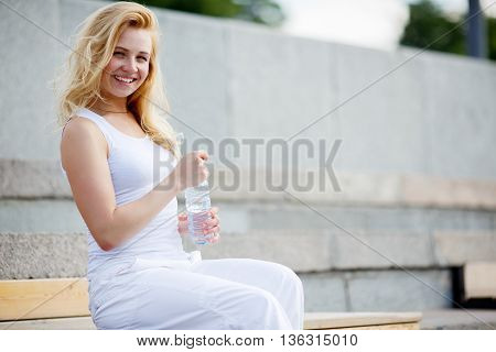 Caucasian woman in light white dress sitting on bench with plastic bottle of water and smiling
