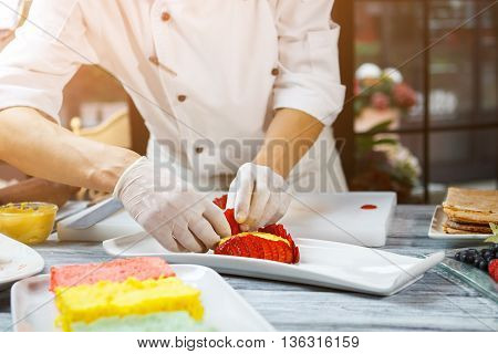 Hands with slices of strawberry. Pieces of berry on plate. Pastry chef cooks flan. Sweet custard and juicy fruit.
