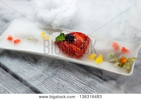 Mint leaf on sliced strawberries. Dessert on long white plate. Flan served with dry ice. High-calorie dish with fruits.