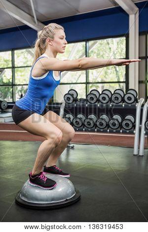 Woman exercising with bosu ball at gym