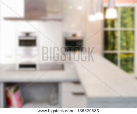 Modern kitchen furnishing with desk oven window and lights blurred.