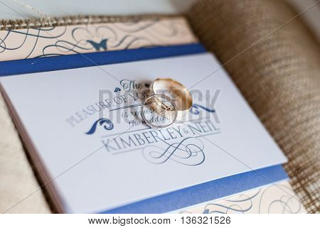 close up of wedding rings sitting on a wedding invitation