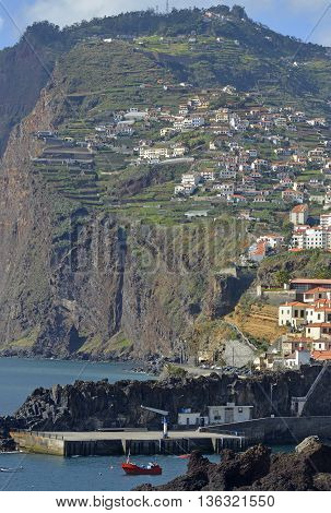 View to Camara de Lobos with high cliffs behind from cliff top walkway. Madeira Portugal