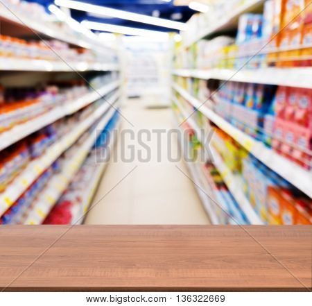 Wooden board empty table in front of blurred background. Perspective dark wood table over blur of baby foods jars in store. Mock up for display or montage your product.