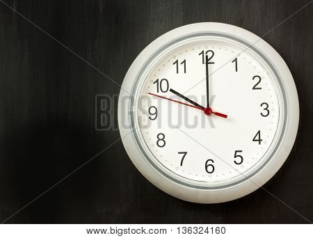'Beginning of workday' or 'time' concept: a photo of a typical white office clock on a dark background with copyspace
