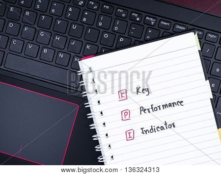 KPI (Key Performance Indicator) on white notebook with laptop keyboard (Business concept)