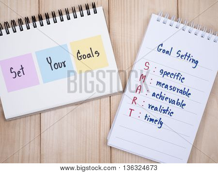 Handwriting Set Your Goals and SMART Goal on notebook with wood background (Business Concept)