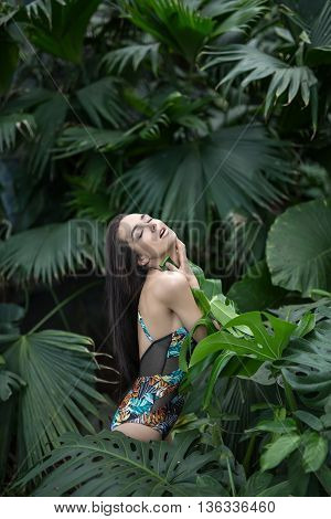 Sensuous girl stands sideways between big green plants. She wears a colorful swimsuit with pictures. She presses big leaf to her body with her hands. Her eyes are closed and mouth is open. Vertical.