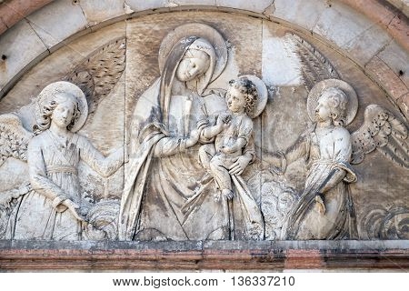 LUCCA, ITALY - JUNE 06, 2015: Bas-relief representing the Virgin Mary with baby Jesus between angels, Cathedral of S.Martino in Lucca, Italy, on June 06, 2015
