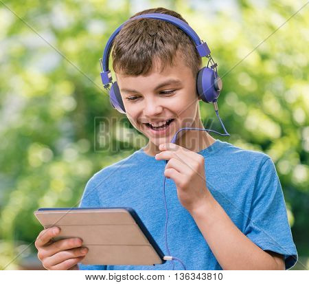 Outdoor portrait of happy teen boy 12-14 year old chating with family or friends using tablet