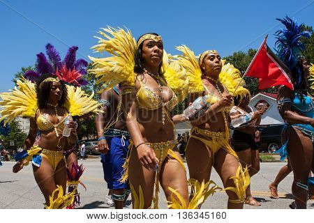 ATLANTA, GA - MAY 2016: Women wearing yellow bikinis and elaborate feathered costumes walk in a parade to celebrate Caribbean culture on North Avenue in Atlanta GA, on May 28 2016 .