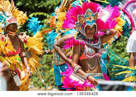 ATLANTA, GA - MAY 2016: Young women wearing elaborate costumes and feathered headdresses walk in a parade to celebrate Caribbean culture along North Avenue in Atlanta GA, on May 28 2016 .