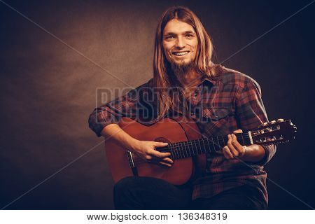 Guitarist trying out chords. Young male musican practicing on guitar. Music instrument passion concept.