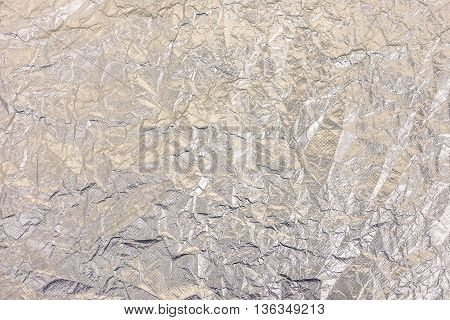 Silver metal aluminum background - Rippled aluminium foil view from above - Dark colors and shadows down to emphasize the metallic material