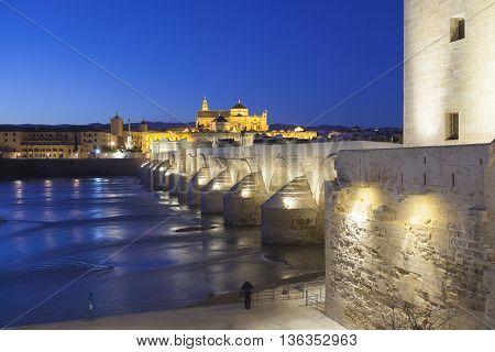 Cordoba - Spain - June 10, 2016 : Roman Bridge On Guadalquivir River And The Great Mosque At Twiligh