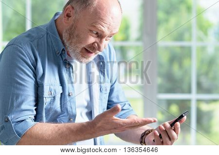 Portrait of a elderly man with phone at home