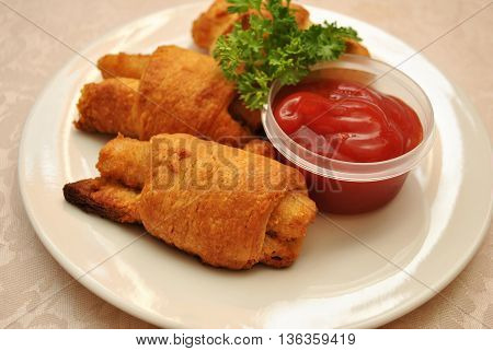 Fish Sticks Wrapped in Golden Croissant Rolls Served with Catsup
