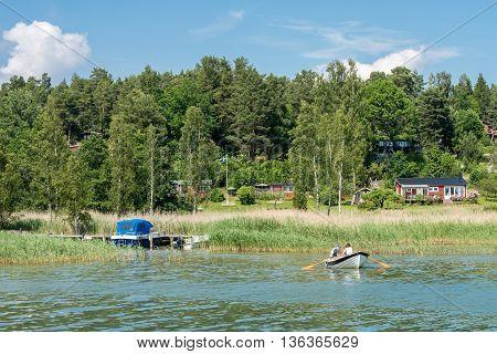 VIKBOLANDET, SWEDEN - JUNE 25, 2016:  People relax in a rowboat during midsummer at Vikbolandet. Midsummer is one of the major holidays in Sweden.