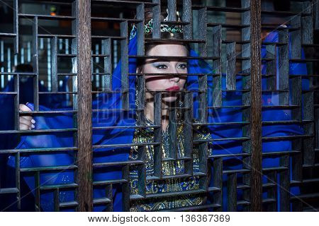 Beautiful Girl In The Turkish National Blue Dress, Looking Out From Behind A Wooden Lattice