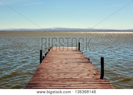 a wooden dock over the lagoon in the Albufera de Valencia, in Valencia, Spain