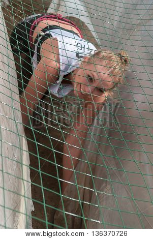 Tyumen, Russia - June 11, 2016: Race of Heroes project on the ground of the highest military and engineering school. Guardroom stage. Girl creeps on an entrenchment with sand and water under net. Focus on grid