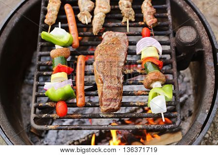 Seasoned New York Strip Steak hotdogs and vegetable shish kabobs are cooking on the grill of an open campfire at a summer picnic.