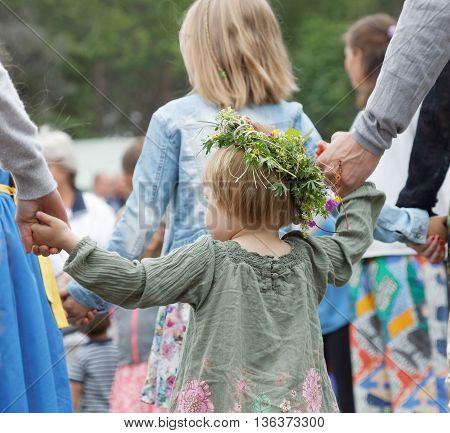 VADDO SWEDEN - JUNE 23 2016: Litte girl wearing flowers in the hair dancing around the maypole celebrating the Midsummer in Sweden June 23 2016