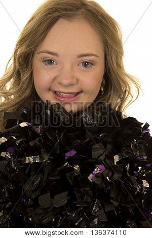 a close up of a cheerleader with her pom poms up by her face she has down syndrome.