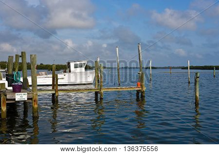 Old White Fishing Boat and Dock on a Bay in Florida