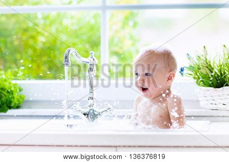 Baby taking bath in kitchen sink. Child playing with foam and soap bubbles in sunny bathroom with window. Little boy bathing. Water fun for kids. Hygiene and skin care for children. Bath room interior