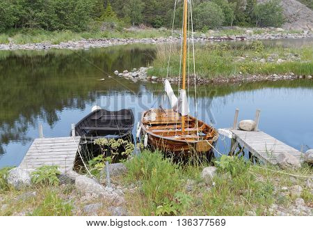 Rural wooden rowboat and sailboat at small bridges in the bay. No people