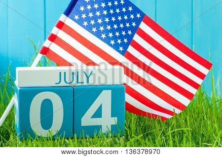 July 4th. Image of july 4 wooden color calendar on blue background with flag of the USA. Summer day. Independence Day Of America.