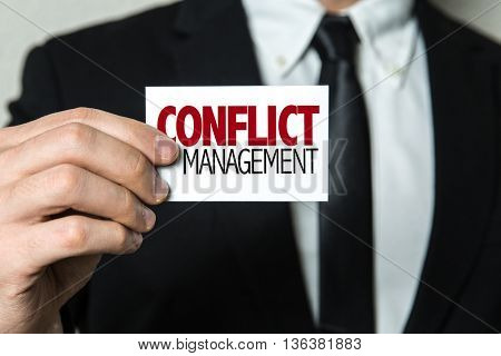 Business man holding a card with the text: Conflict Management