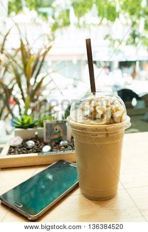 Latte frappe topping with whipping cream in takeaway cup and mobile phone on table in coffee shop.