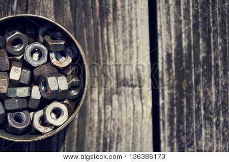 Nuts In A Tin Can On Wooden Board Background