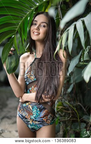 Smiling girl with loose hair stands near the wall with big green plants. She wears a colorful swimsuit with pictures. She holds big leaf with the right hand, left hand is on the right hip. She looks into the camera. Vertical.