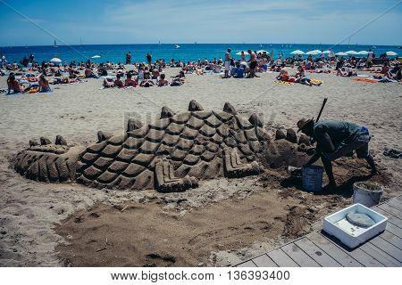 Barcelona Spain - May 24 2015. Man creates a sand sculpture at Barceloneta beach