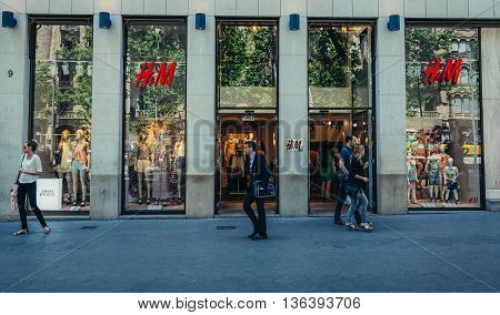 Barcelona Spain - May 26 2015. People walks in front of H&M shop located at Passeig de Gracia one of the major avenues in Barcelona