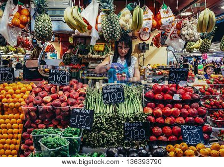 Barcelona Spain - May 26 2015. Woman sells fruits and vegetables at public market called La Boqueria foremost tourist landmarks in Barcelona