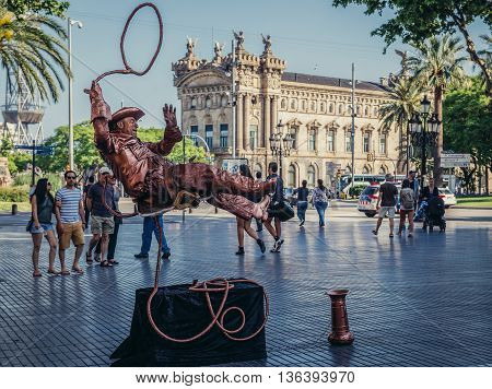 Barcelona Spain - May 26 2015. Man dressed as cowboy gives live statue performance at famous La Rambla street