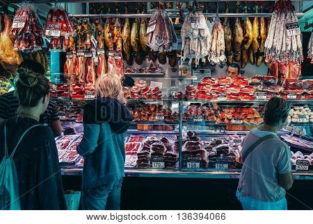 Barcelona Spain - May 28 2015. Clients looks at dry cured ham called jamon at public market La Boqueria foremost tourist landmarks in Barcelona
