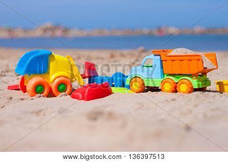 Сhildren's toy on the sand on the beach near the sea