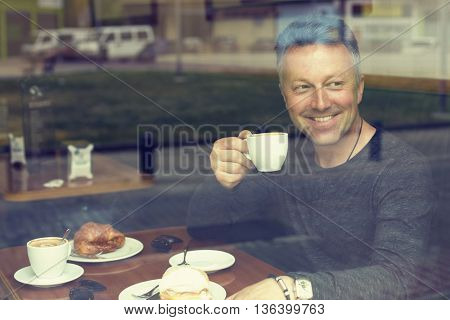Attractive smiling mid adult man drinking morning coffee in cafe, image toned.