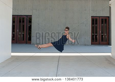 Teen girl with crew cut floating supine in air.