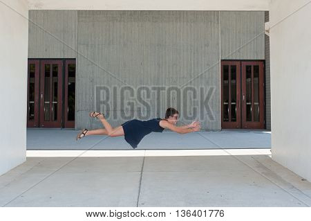 Teen girl with crew cut floating prone in air.