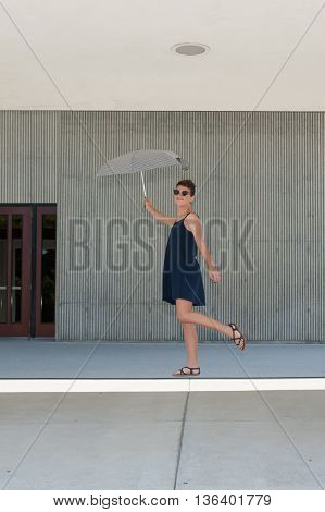 Teenage girl with crew cut and sunglasses levitating with umbrella.