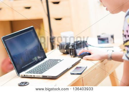 Goodlooking young asian man relaxing at home in wood chair sitting in living room with laptop computer and coffee drink